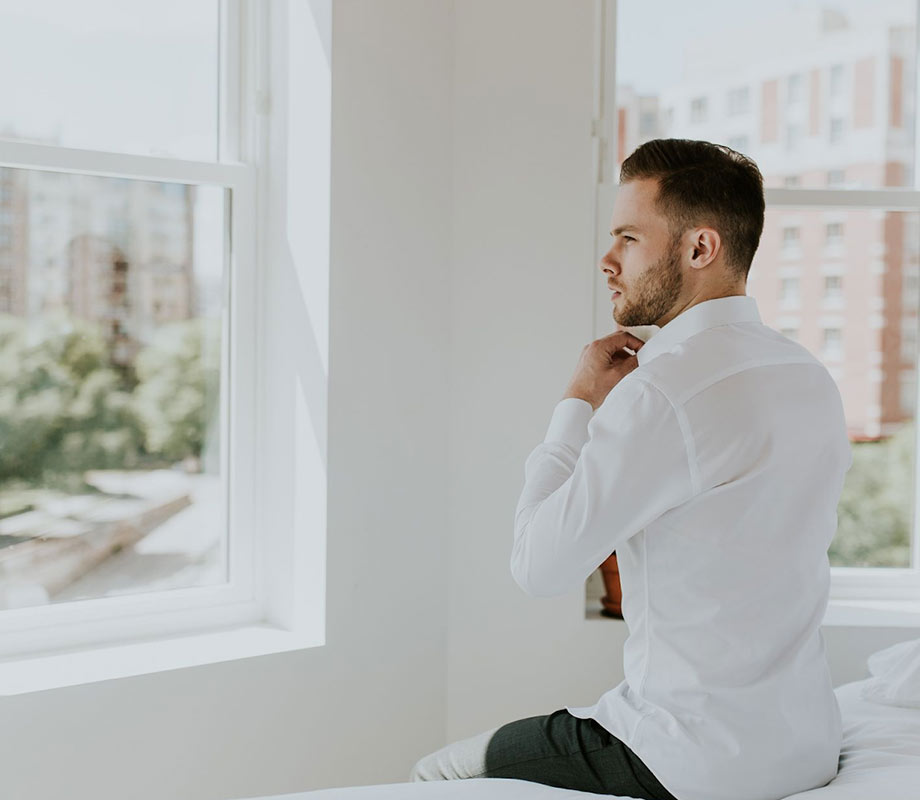 young man in white dress shirt sitting on bed looking out