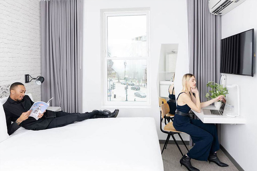 Couple in hotel room. Guy reading magazine on bed, girl on laptop at desk